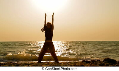 Young Woman Practicing Yoga On Sandy Beach At Sunset -...