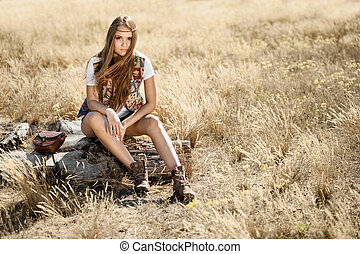 Beautiful young hippy girl sitting on a tree stump -...