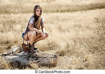 Beautiful young hippy girl sitting on a tree stump at midday...