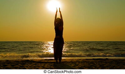 Girl Practicing Yoga On The Beach At Sunset - This is a...