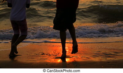 Boy And Girl Dancing On The Beach At Sunset