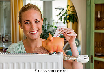 woman with radiator and piggy bank - a young woman with a...