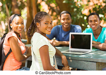 group of african college student relaxing outdoors and...