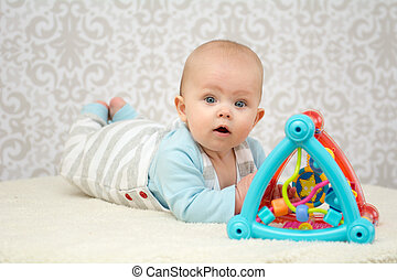 Blue eyes baby playing with toy - Blue eyes baby girl lying...