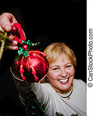 Mature Woman hanging Christmas Ornament