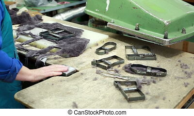 Worker cuts fur details for footwear production - View of...