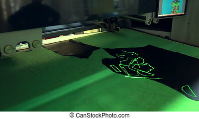 Robotic machine cuts leather with laser marking - View of...