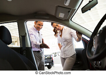 car dealer showing new car to customer - friendly car dealer...