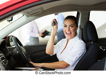 young woman showing her new car key - cheerful young woman...