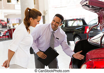 car salesman showing new vehicle to customer - handsome car...