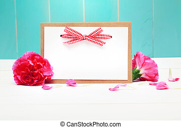 Card with carnations on teal colored wood - Card with...