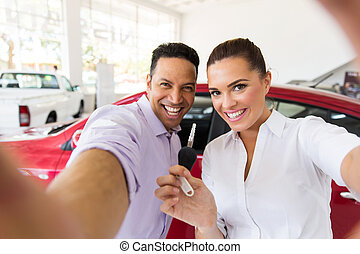 couple taking selfie together at dealership - happy couple...