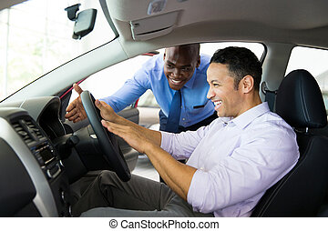 african salesman explaining car features to customer -...