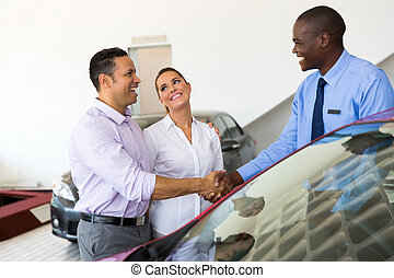 african car salesman handshaking with couple