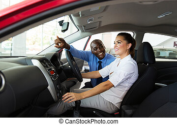 salesman explaining car features to young female customer