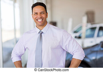 middle aged salesman standing at car dealership - happy...