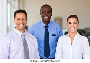group of car dealership staff standing in showroom