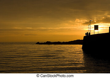 Sunset silhouette at harbour in Elie, East Neuk, Fife,...