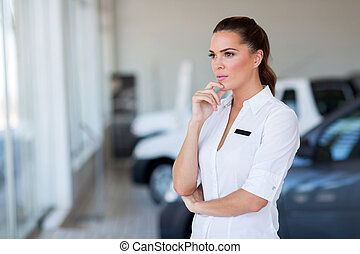 thoughtful female car dealership principal standing in...
