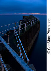 Harbour wall and lighthouse in picturesque fishing village of Pittenweem, East Neuk, Fife, Scotland, UK, at dusk