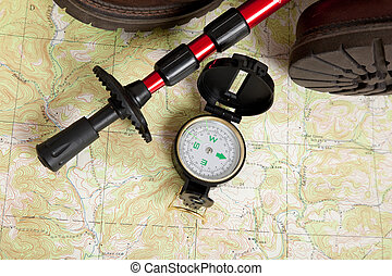 Compass laying on a map with a hiking stick and boots