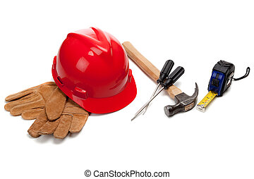 A red hard hat and leather work gloves with tools on white