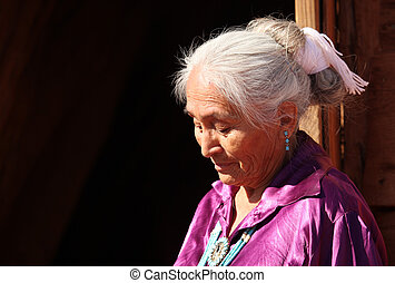 A Navajo Woman Looking Down Outdoors in Bright Sun