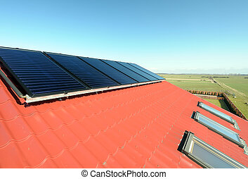Closeup of solar panels on red roof with small windows. Beautiful blue sky and green field in background.
