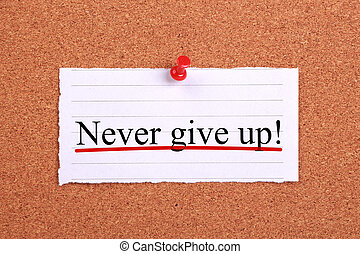 Never give up text paper is pinned on cork.