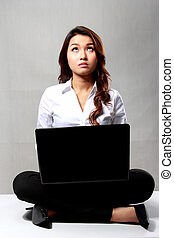 Young businesswoman thinking while working with a laptop