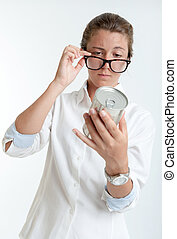 Nutrition exam - Young woman inspecting an aluminum can...
