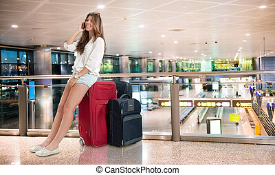 Waiting at the airport - Young woman sitting on her suitcase...