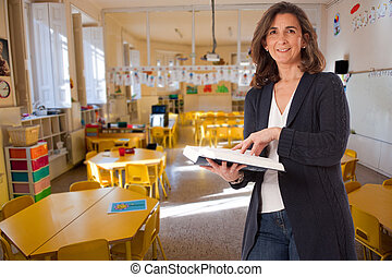 Elementary school teacher - Smiling woman holding a book in...