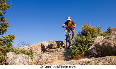 Mountain biking - A young man riding a mountain bike outdoor