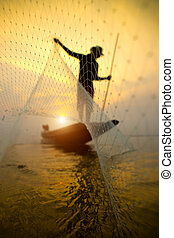 Silhouettes fisherman throwing fishing nets during sunset -...