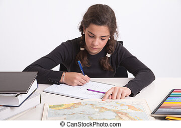 Geography homework - Young girl with a serious expression...