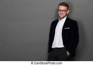 Young businessman leaning on the wall in work suit