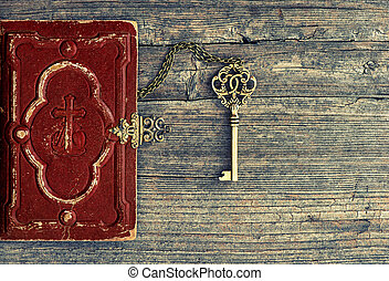 Antique bible book and golden key on wooden background