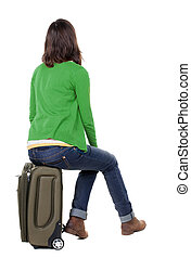 back view of walking woman in cardigan sits on a suitcase....