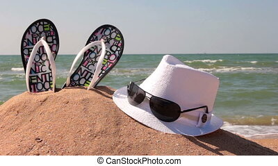 Relax on the beach - Hat, sunglasses and flip flops on the...