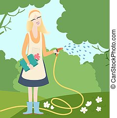 Young woman watering flowers in a garden - A young woman...