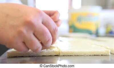 hands prepare a sandwich with cheese and ham