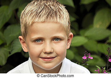 Portrait of young boy with blond hair and blue eyes -...