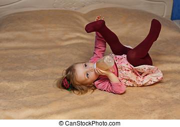 Little girl drinking from a feeding-bottle