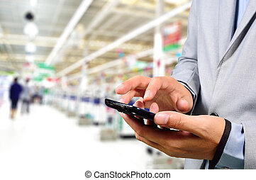 Business Man using mobile phone while shopping in...