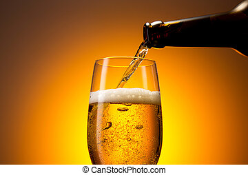 pouring cold beer in a glass - A bottle pouring beer out in...