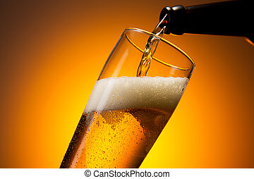 fresh cold beer is pouring in to a glass - A bottle of beer...