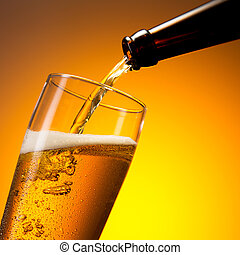 beer flows in to a cold glass - A bottle of beer flows cold...