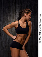 Mixed race sporty woman demonstrating biceps and slim figure...