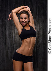 Smiling mixed race sporty woman demonstrating her figure -...